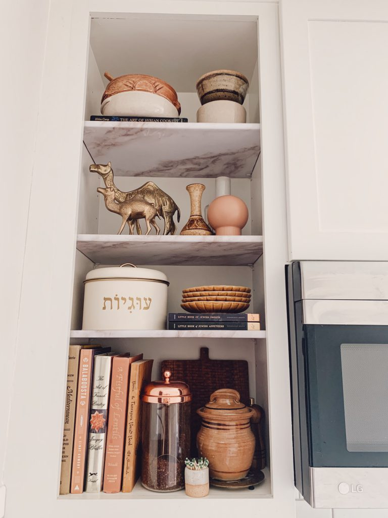An open kitchen shelf, with faux marble contact paper shelf coverings and decor.