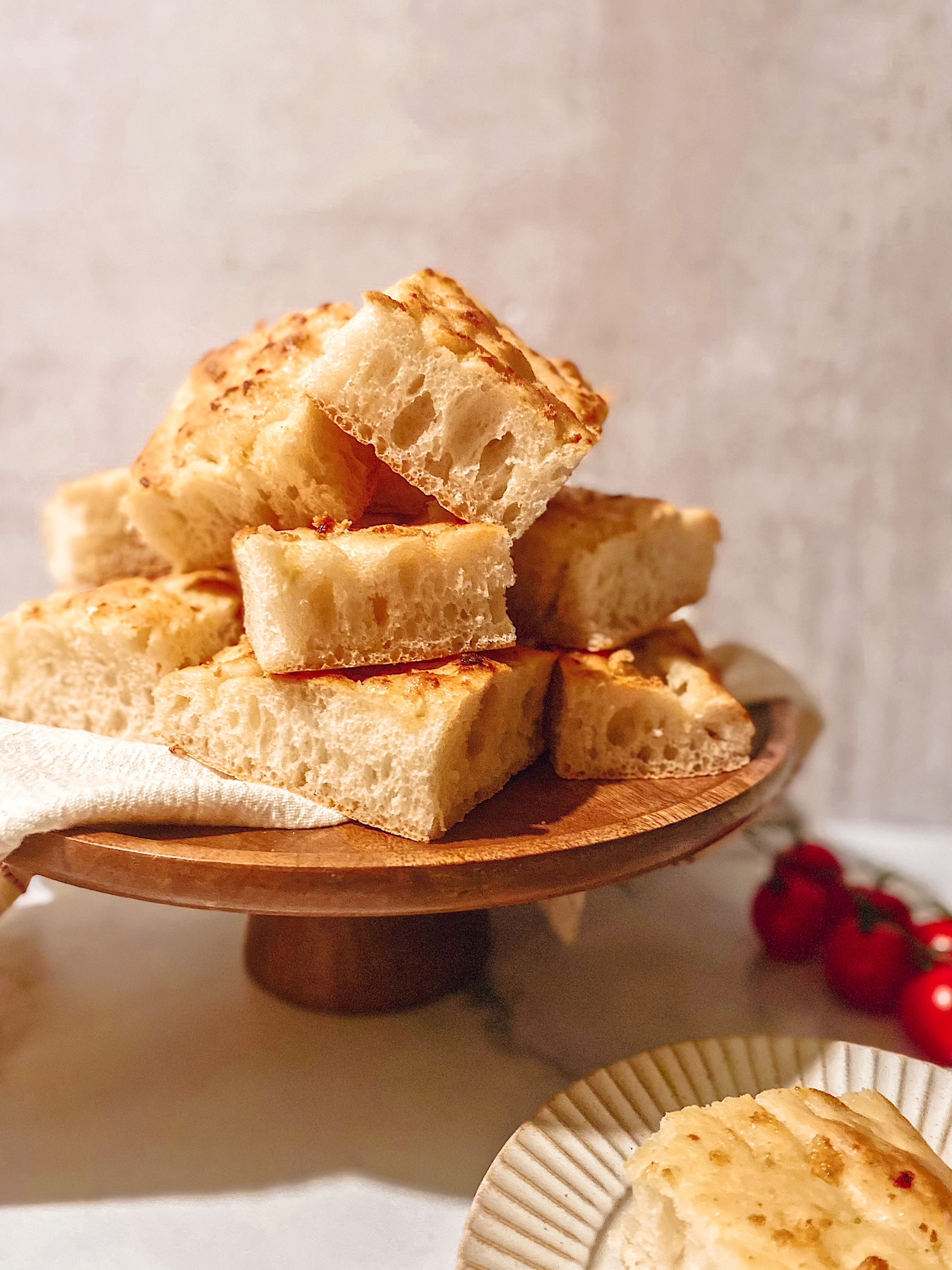A wooden plate of garlic topped Lebanese talami bread.